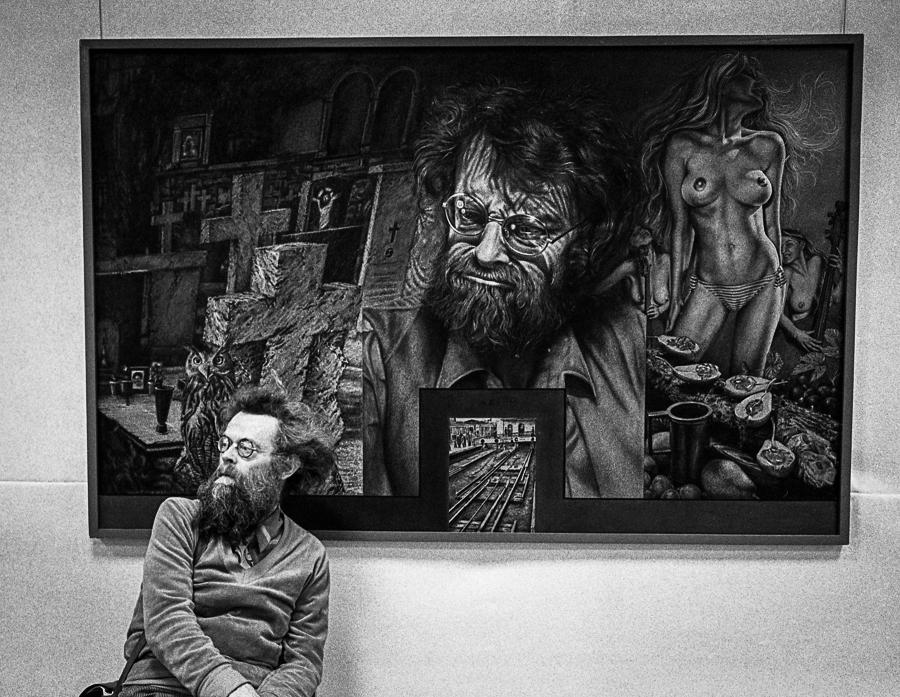 Werner Spribille sitzt vor seinem Portrait, das Erik Mälzner gemalt hat
